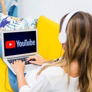 יוטיוברית יושבת מול מסך הרשום עליו יוטיוב המסמל נקודת מבט על חיי יוטיוברים