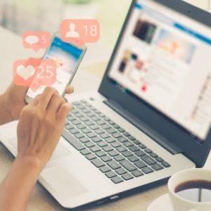 ידיים מחזיקות טלפון נייד ותגובות על תוכן שבפורסם כחלק מרעיונות לפרסום תוכן במדיה החברתית על רקע של לפטופ ובו פייסבוק פתוח