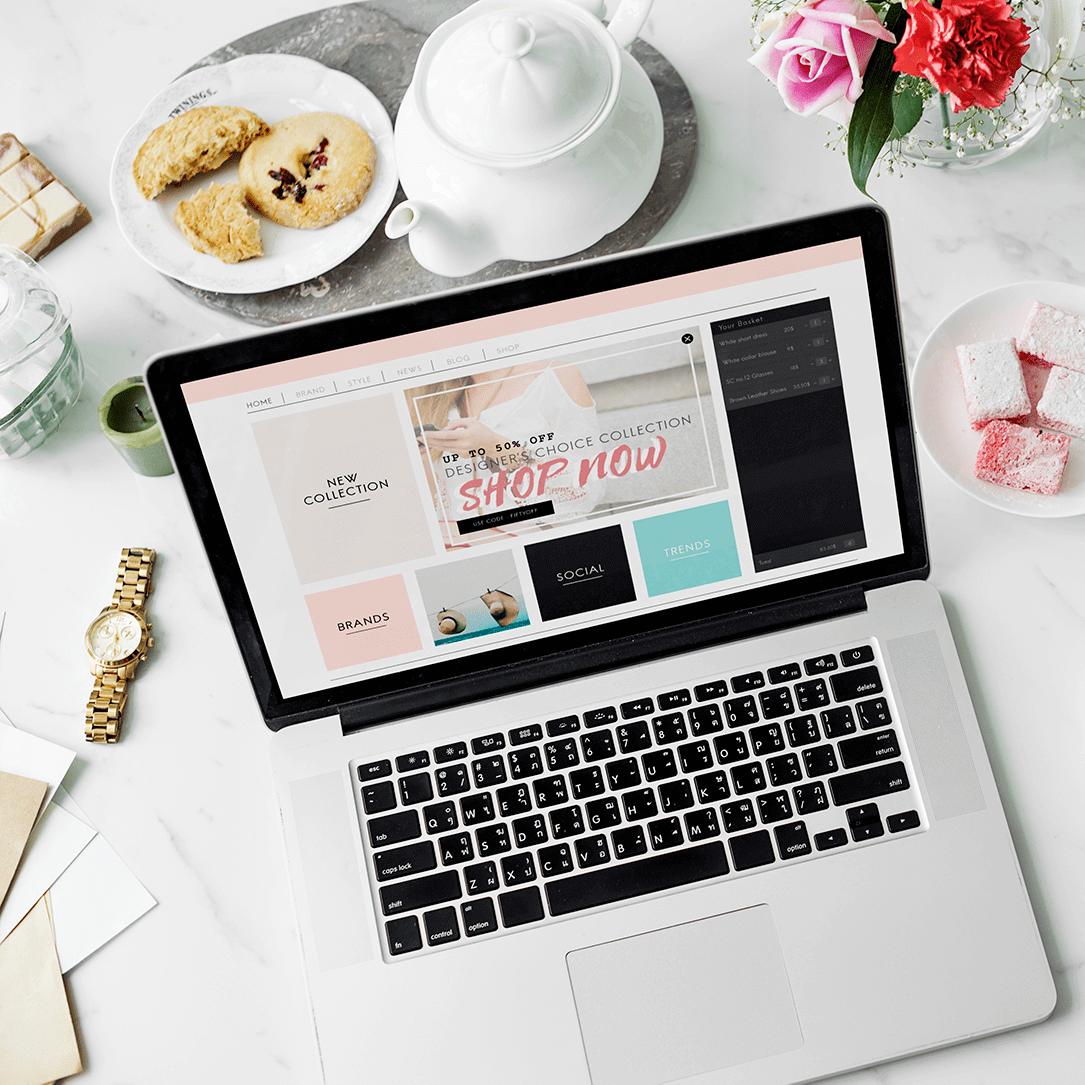 לפטופ פתוח עם אתר תדמיתי המראה למה העסק שלכם צריך אתר ומסביבו פריטי משרד בית על שולחן לבן